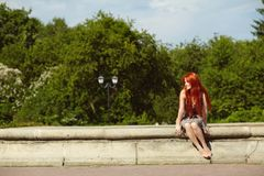 Portrait af a beautiful redhead woman outdoors. stylish romantic young girl on a walk in the park. Red hair stock image