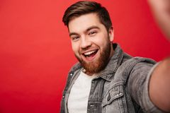 Portrait of affable kind man 30s in jeans jacket looking on came. Ra with amazing smile while taking selfie  over red background Royalty Free Stock Images