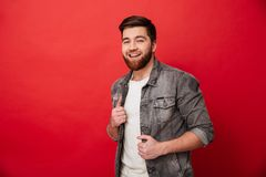 Portrait of affable kind man 30s in jeans jacket posing on camer. A with amazing smile  over red background Stock Photography