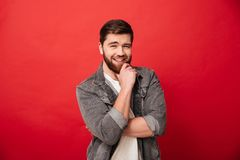 Portrait of affable kind man 30s in jeans jacket posing on camer. A touching chin with beautiful smile isolated over red background Stock Image