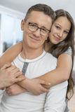 Portrait of affectionate girl embracing father from behind at home Royalty Free Stock Images