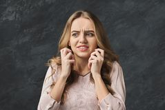 Portrait of afraid young woman. Scared girl grimacing and gesturing on gray studio background Stock Photo