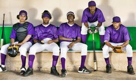 Portrait of african american baseball players sitting side by side in dugout