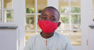 Portrait of african american boy wearing face mask outdoors on a bright sunny day