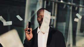 Portrait of african american businessman looking at camera while money flying down all over the place. He holding. Smartphone in hands. Money rain on the stock video footage
