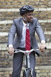 Portrait of African American businessman riding Bicycle royalty free stock images