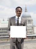 Portrait of African American businessman smiling and holding blank cardboard Royalty Free Stock Photos