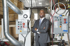Portrait of African American businessman standing arms crossed with machinery in background Stock Photo