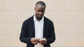 Portrait of african american businessman in suit counting money standing near office centre. He celebrating his. Successful win with a lot of dollars and stock footage