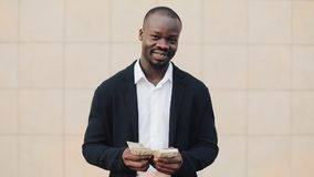 Portrait of african american businessman in suit counting money standing near office centre. He celebrating his. Successful win with a lot of dollars and stock video