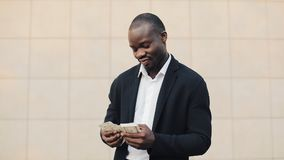 Portrait of african american businessman in suit counting money standing near office centre. He celebrating his. Successful win with a lot of dollars and stock video footage