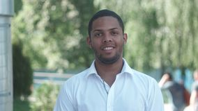Portrait of African American businessman in white shirt smiling outdoor at park stock footage