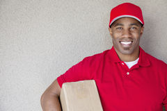 Portrait of a African American delivery man holding package against wall Royalty Free Stock Image