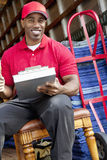 Portrait of a African American delivery man sitting on chair with clipboard Stock Image