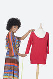 Portrait of African American female designer measuring a red tunic over gray background Stock Image
