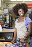 Portrait of an African American female store clerk standing at checkout counter scanning item Stock Photos