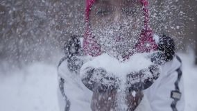 Portrait of african american girl dressed warm wearing beanie hat and white jacket blowing snowflakes from hands into. Portrait of african american girl blowing stock video footage