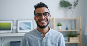 Portrait of African American guy in glasses looking at camera smiling indoors stock video