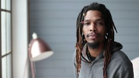 Portrait of african american hipster smiling. Portrait of african american hipster with dreadlocks looking at the camera and smiling in domestic interior stock footage