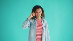 Portrait of African American lady twisting finger at temple making fool sign. Looking at camera standing alone on blue background. People and attitude concept stock video