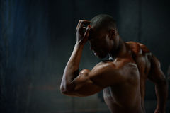 Portrait. African american male body builder posing on a black studio background. Beauty and perfection of human body.  stock photography