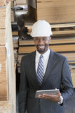 Portrait of African American male contractor using tablet PC with wooden planks in background Stock Images