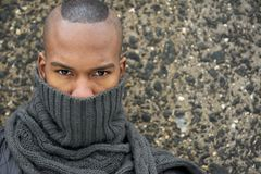 Portrait of an african american male fashion model with gray scarf covering face. Close up portrait of an african american male fashion model with gray scarf stock photos