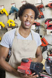 Portrait of an African American male store clerk holding electronic tool Royalty Free Stock Photos
