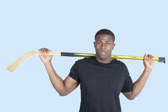 Portrait of an African American man holding hockey stick over blue background Royalty Free Stock Photo