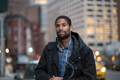 Portrait of African American man listening to music in the city Stock Image