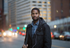 Portrait of African American man listening to music in the city Royalty Free Stock Image