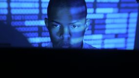 Portrait of african american man programmer coding network security software. Hacker typing code on computer screen in. A dark office at night stock video