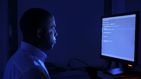 Portrait of african american man programmer coding network security software. Hacker typing code on computer screen in. A dark office at night stock video footage