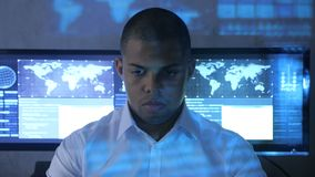 Portrait of African American man programmer in white shirt working on computer in security data center. Holographic code. Portrait of African American man stock video footage