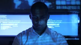 Portrait of African American man programmer in white shirt working on computer in security data center. Holographic code. Portrait of African American man stock footage