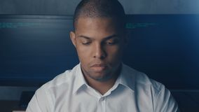 Portrait of African American man programmer in white shirt working on computer in security data center. Portrait of African American man programmer in white stock video