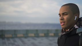 Portrait of african american man in stylish earphones walking on urban embankment. Ethnic male talking to bass about career using digital devices and smiling stock footage