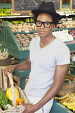 Portrait of an African American man with vegetable basket at supermarket Royalty Free Stock Image