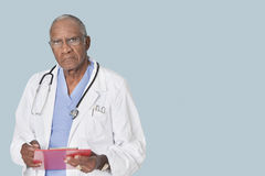 Portrait of an African American senior doctor holding clipboard over light blue background Stock Photography