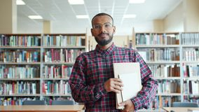Portrait of African American student walking in university library with books