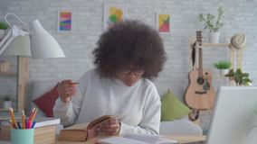 Portrait african american students woman with an afro hairstyle. Engaged at home stock footage
