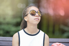 Portrait of African American Teenager With Long Dreadlocks Posing in Park Outdoors in Sunglasses Stock Photos