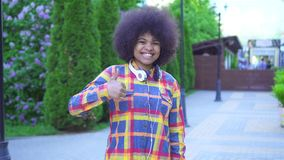 Portrait african american woman with an afro hairstyle with approval shows a finger up. Standing on the street stock video footage