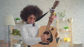 Portrait african american woman with an afro hairstyle expressive playing on the guitar. Portrait beautiful african american woman with an afro hairstyle stock video footage
