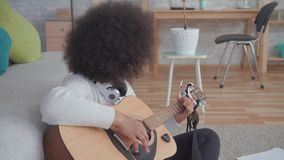 Portrait african american woman with an afro hairstyle plays guitar sitting on the floor. In a modern apartment stock video