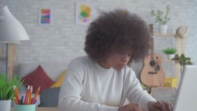Portrait African American woman with an afro hairstyle uses a laptop at home. Portrait beautiful African American woman with an afro hairstyle uses a laptop at stock video