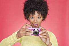 Portrait of an African American woman holding a camera over colored background Royalty Free Stock Photography