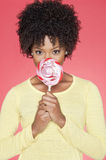 Portrait of an African American woman holding candy over colored background Stock Photo