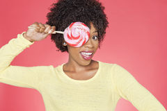 Portrait of an African American woman holding candy over her eye against colored background Stock Photos