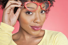 Portrait of an African American woman holding retro glasses over colored background Royalty Free Stock Photography
